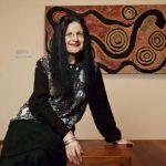 Judith Ryan with Warna Jukurrpa (snake dreaming) by PeterJapanangka Blacksmith. Photo via theage.com.au
